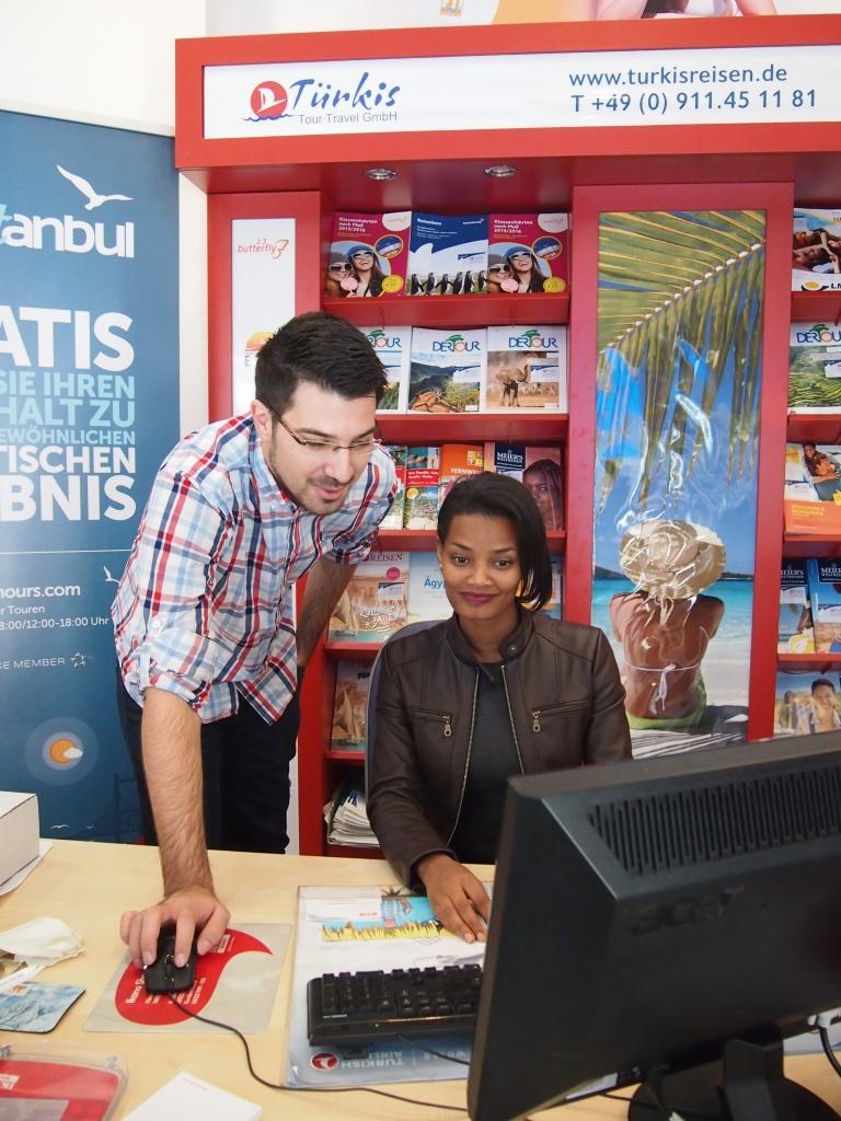 Kollegencoaching: Umut Ulus von Türkis Tour Travel GmbH weist Asfaw Selato in die Buchungssysteme ein